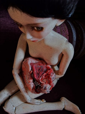 Anorexic doll holding a heart