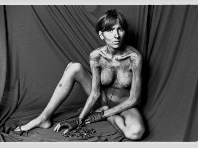 Self-Portrait. Naked and in black painted body, I'm seating and watching at the camera with sad and melancholic expression. My Body very thin, exhibits thin legs and arms and in between there are 6 miniatures horses on the floor, Apocalypse's symbol.